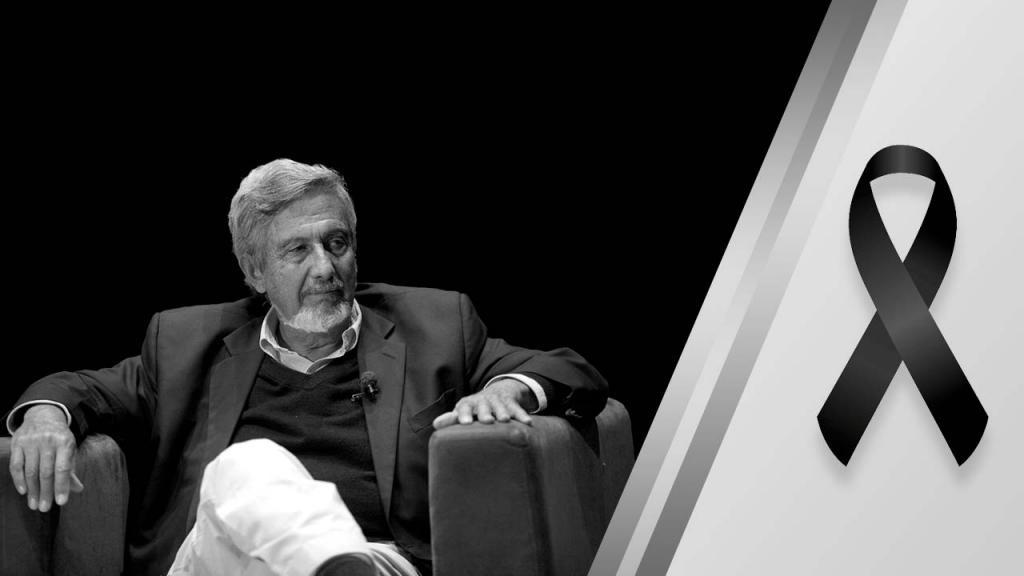 Guillermo Perry, economista colombiano sentado en una silla. A un lado de la imagen una cinta negra por su fallecimiento.