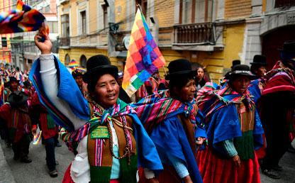 Mujeres indígenas Aymara de Bolivia caminando con banderas.