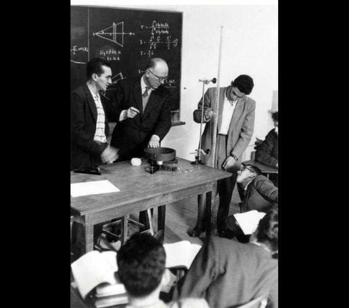 tres hombres en un salon haciendo un experimiento. La foto es antigua y en blanco y negro