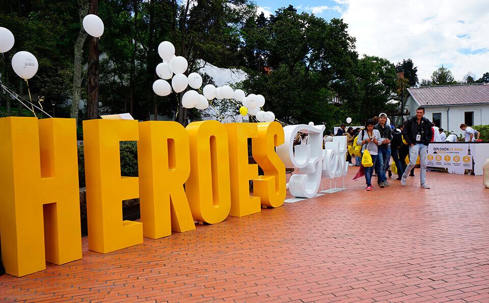 letrero amarillo con blanco que dice heroes fest en campus de los andes