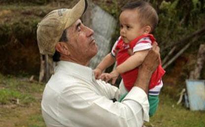 Hombre campesino levantando un bebé