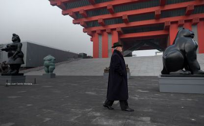 hombre mayor con gabán camina por unas obras de Botero en China