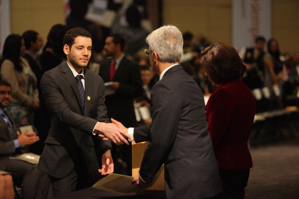 joven de traje negro y corbata de rayas estrecha la mano de un hombre mayor al recibir diploma