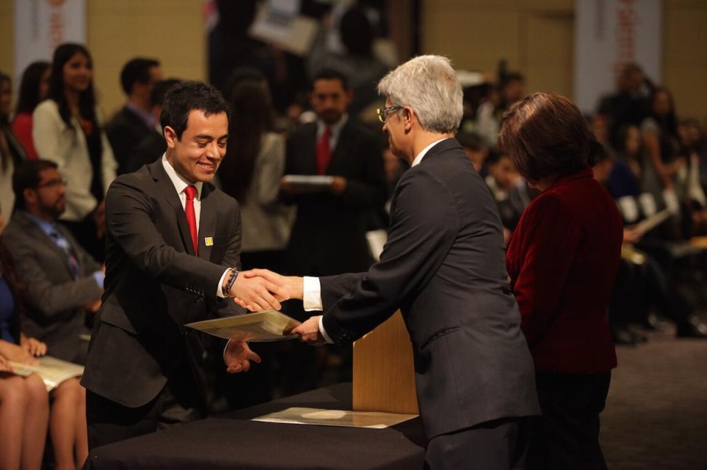 hombre de traje y corbata roja recibe diploma de grado