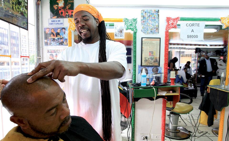 un peluquero está cortando el pelo a otro hombre. El peluquero tiene dreads