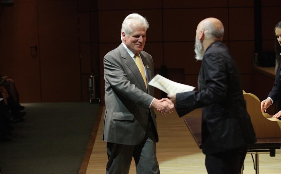 un hombre mayor de corbata amarilla recibe diploma y estrecha la mano de un hombre mayor de traje negro