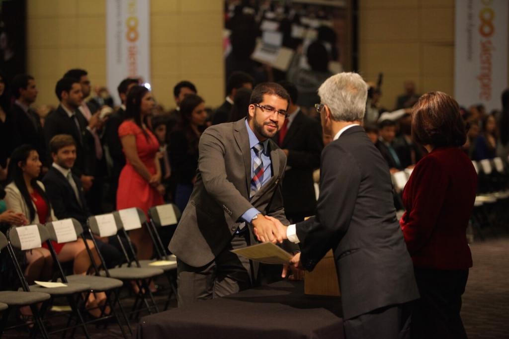 joven de traje gris y camisa azul estrecha la mano de un hombre que le entrega su diploma de grado