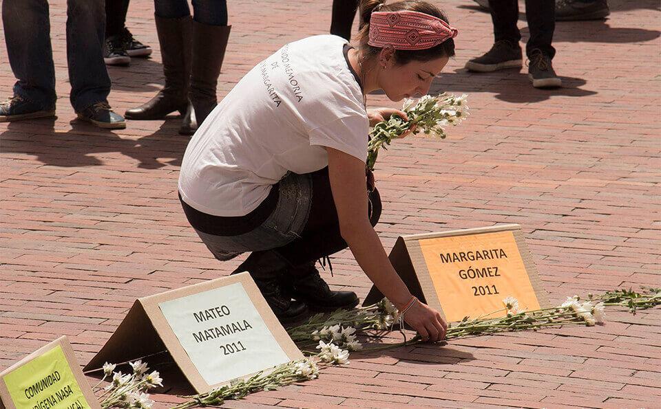 mujer estudiante pone flores en el piso con letreros en honor a las víctimas del conflicto armado