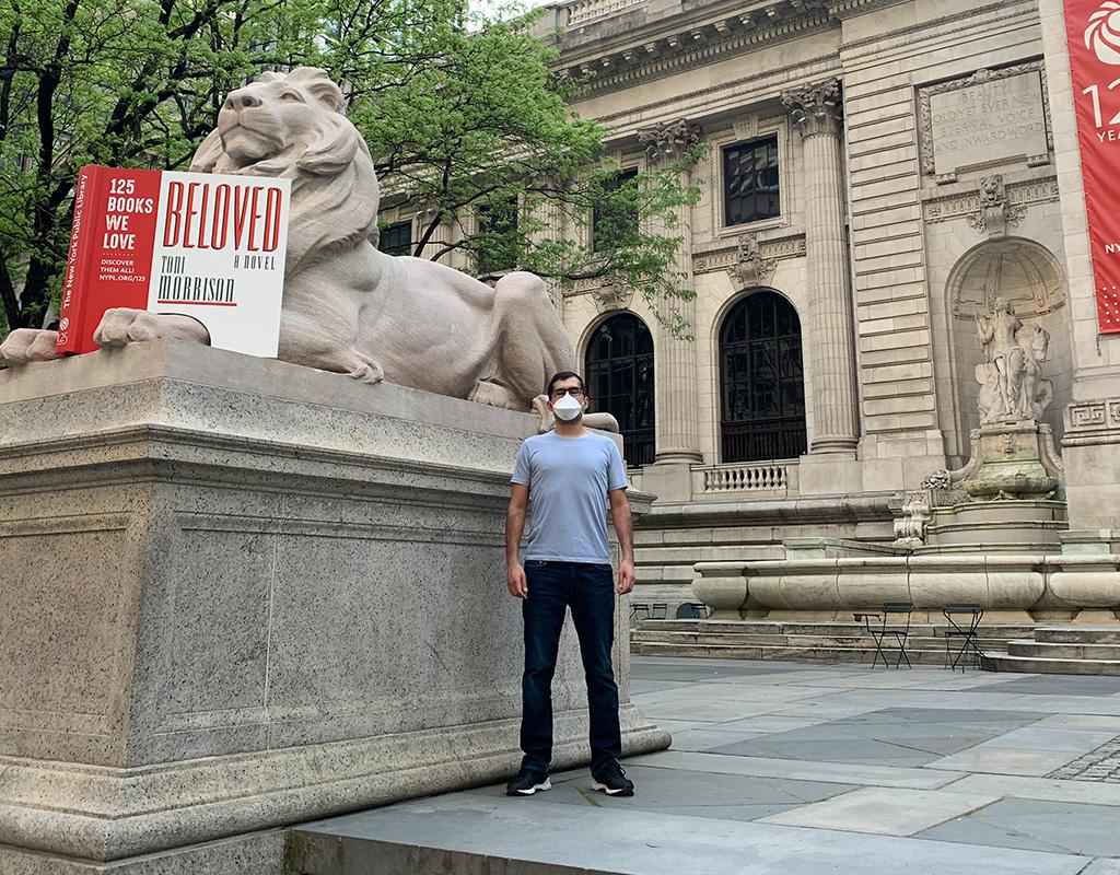 Daniel Téllez posa frente a uno de los leones a la entrada de la Biblioteca Pública de Nueva York.