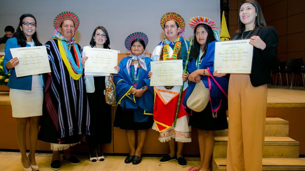 Retrato de una familia indígenas y estudiantes que sostienen diplomas