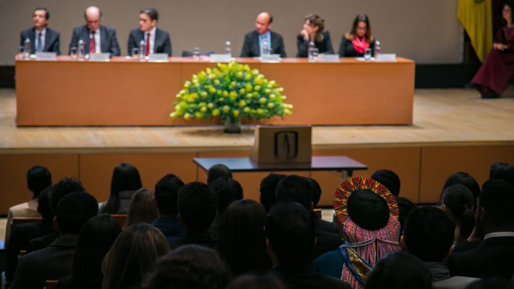 Seis personas sentadas en la tarima de un teatro en una ceremonia de graduación.