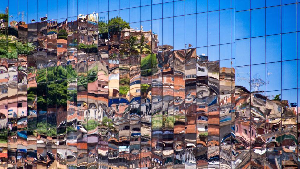 Una favela se refleja en los vidrios de un edificio lujoso.