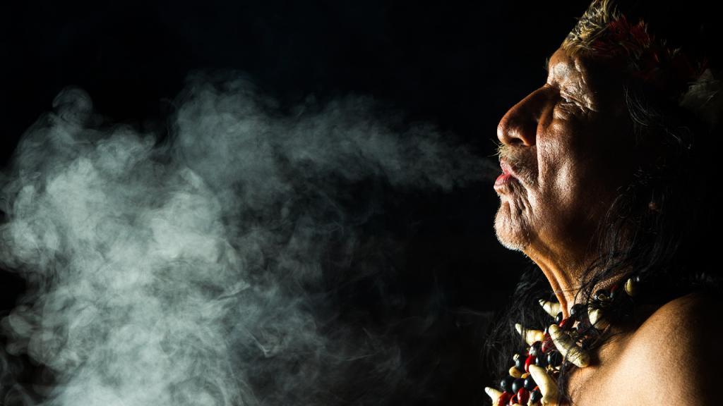 Hombre indígena fumando tabaco.