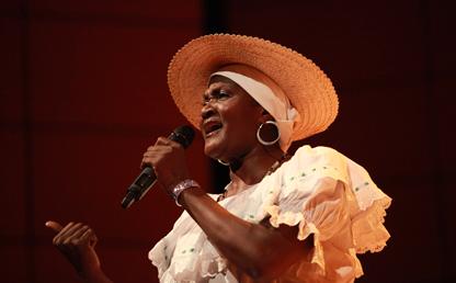 Mujer afrodescendiente canta en un auditorio