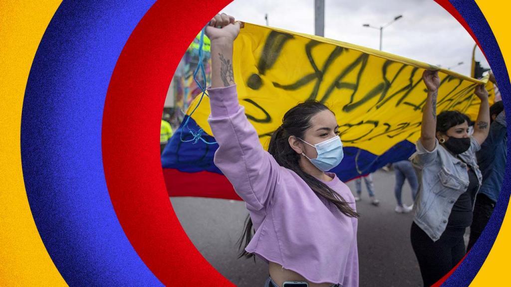 Mujer en protesta. Atrás, la bandera de Colombia.