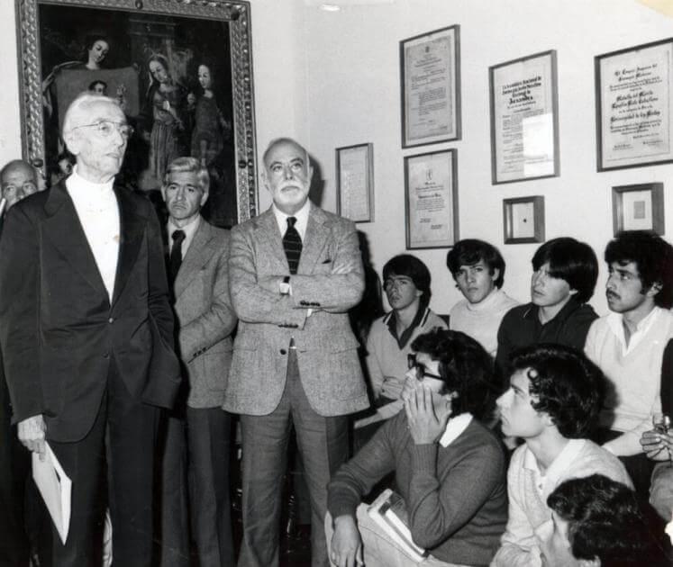 profesores mayores extranjeros en salon hablando a los uniandinos. La foto es antigua y en blanco y negro
