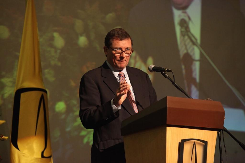 un hombre mayor de gafas da un discurso en una ceremonia, atrás vemos la bandera de la universidad de los andes