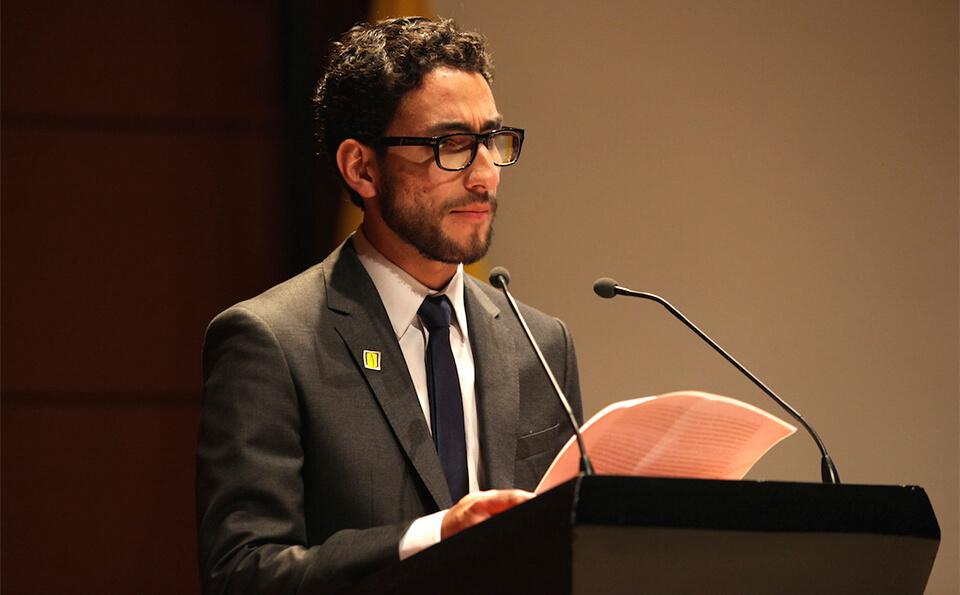 un joven con traje y corbata negra da un discurso frente a un micrófono en sus manos sostiene varias hojas