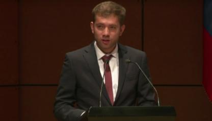 José Luis Cala Estupiñán, frente a atril, ofrece discurso de grado