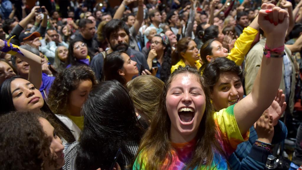 Mujer joven gritando y con la mano arriba.
