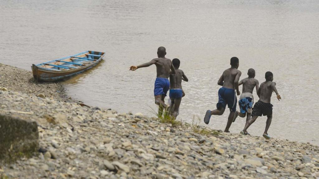 Jóvenes en Buenaventura corren hacia el mar pacífico.