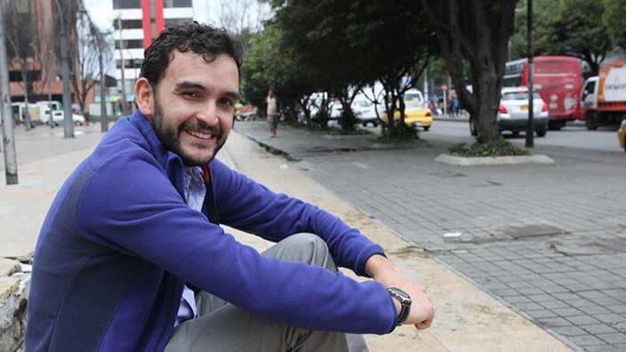 Un hombre sentado en un andén en la calle, viste pantalón gris y saco azul