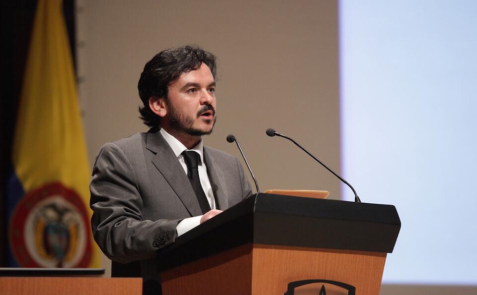 un hombre de traje gris y negro está de pie dando un discurso tras un atril