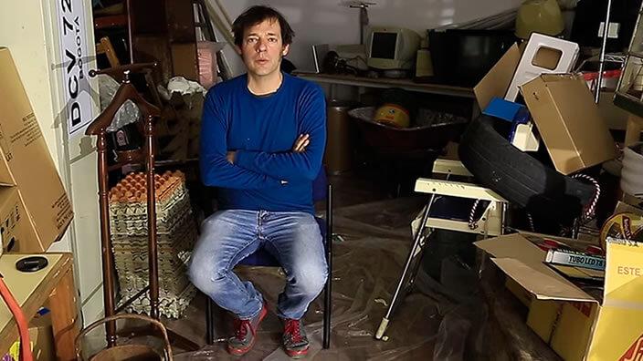 un hombre con jean y camiseta azul está sentado en medio de un taller de artes plásticas