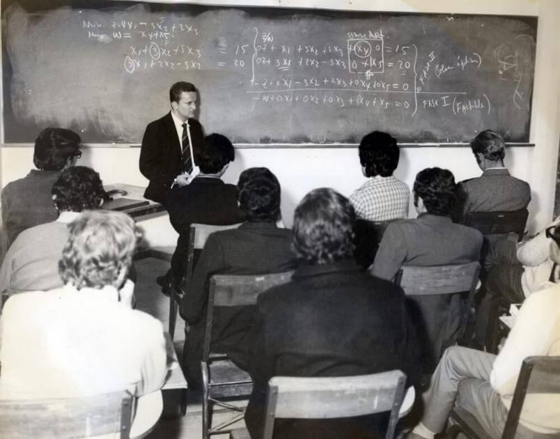 Hombre de traje sentado sobre una mesa da una clase a estudiantes en un salón. La foto es antigua y en blanco y negro
