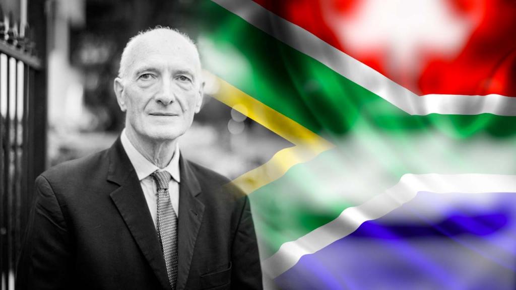 Hombre con la bandera de Sudáfrica de fondo.