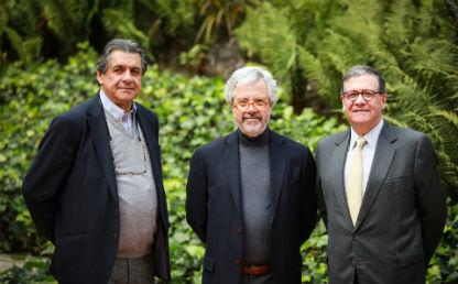 tres hombres con sus brazos en la espalda miran a cámara, los tres visten de tonos grises, atrás de ellos vemos arbustos