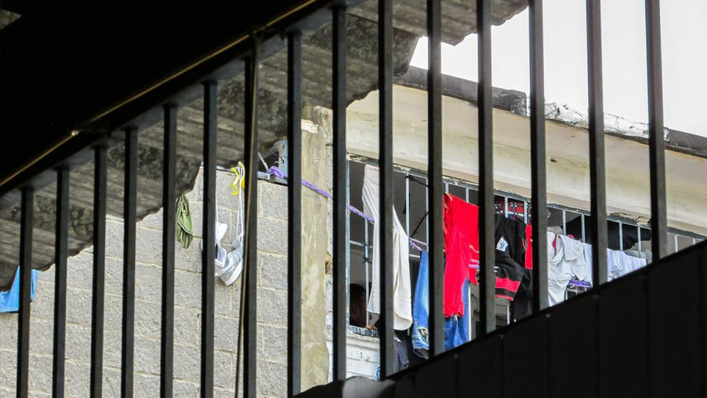 Una ventana abarrotada, detrás de la que se pueden ver prendas de vestir colgadas.