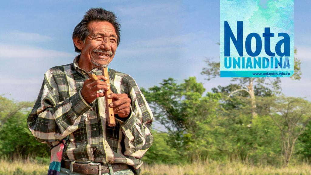 Hombre indígena tocando una flauta.