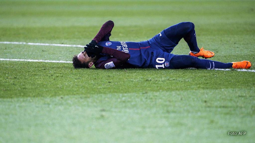 El futbolista Neymar lesionado postrado en el césped se toma la cara con dolor. Foto: AFP