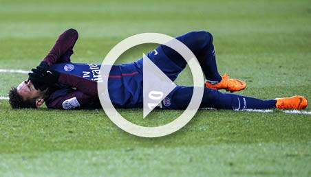 Futbolista lesionado postrado en el cesped se toma la cara con dolor