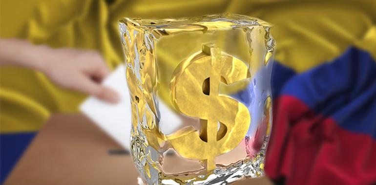 Signo pesos entre un bloque de hielo, de fondo la bandera de Colombia y una mano votando.