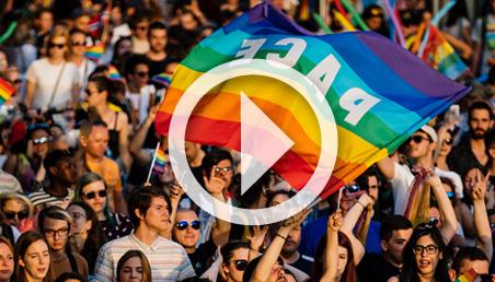 Hombres y mujeres sostienen bandera multicolor, de la comunidad LGBT.
