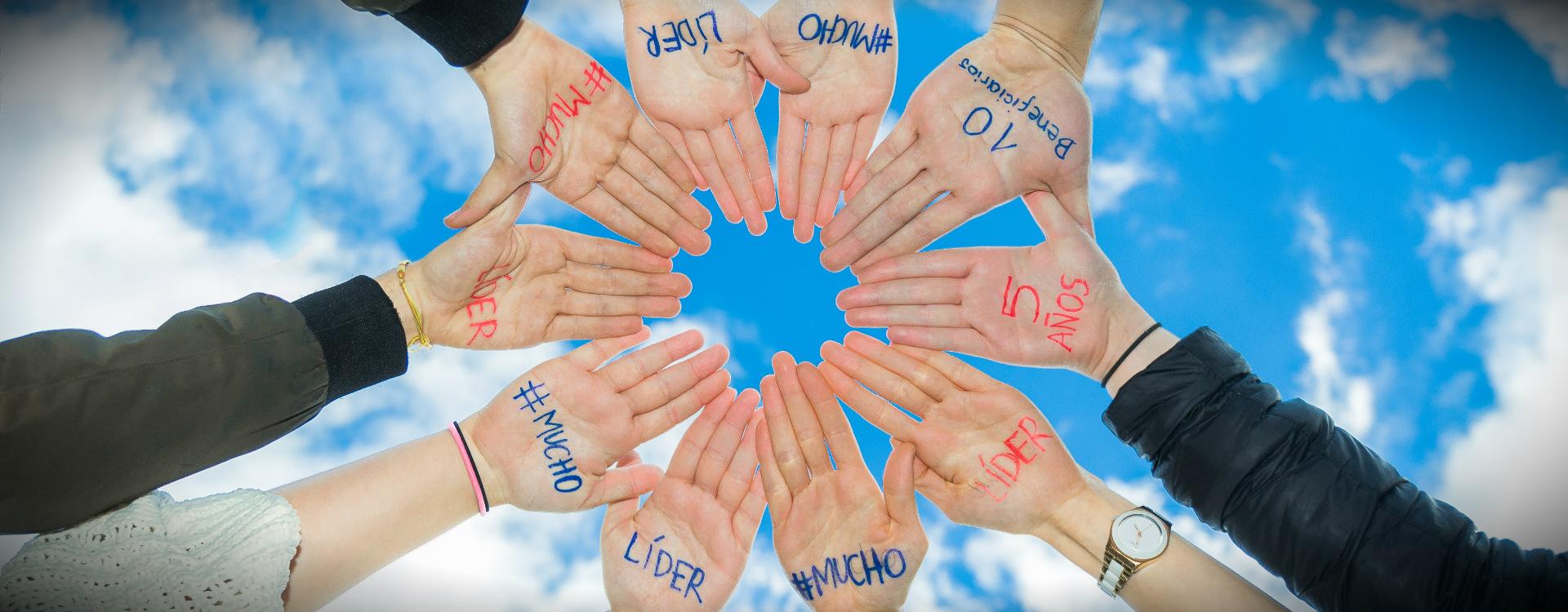Manos de jóvenes con las palabras Mucho Líder y 10 beneficiarios con el cielo de fondo