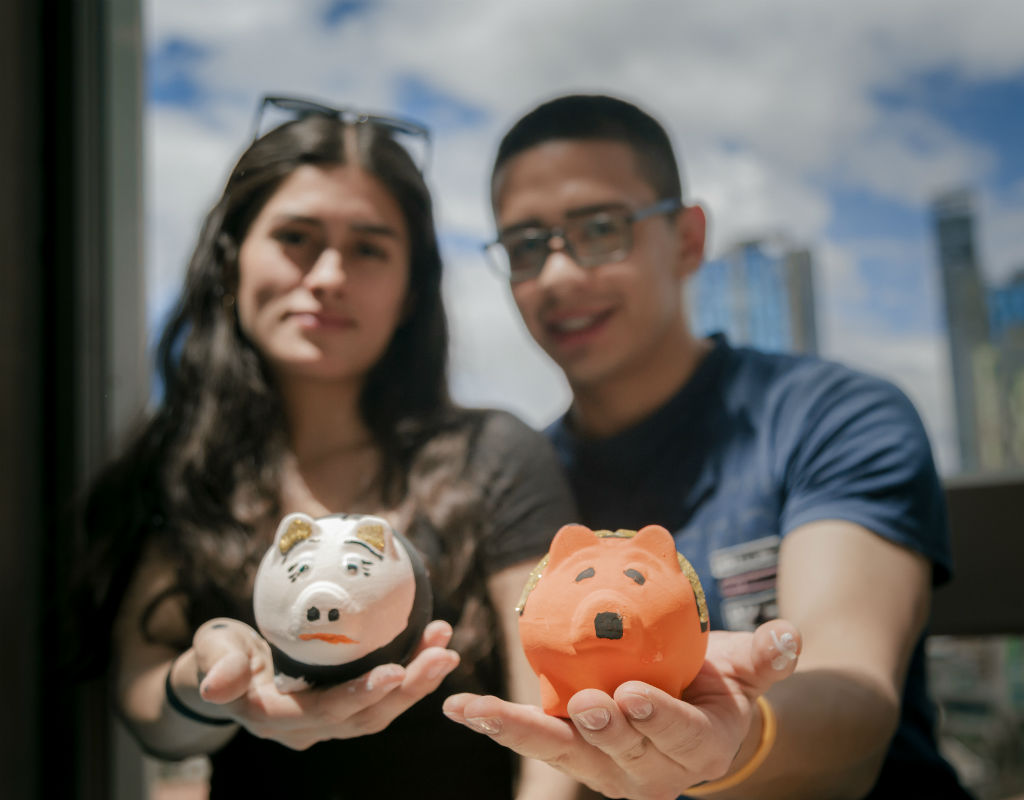 Imagen de 2 estudiantes sosteniendo alcancías en sus manos