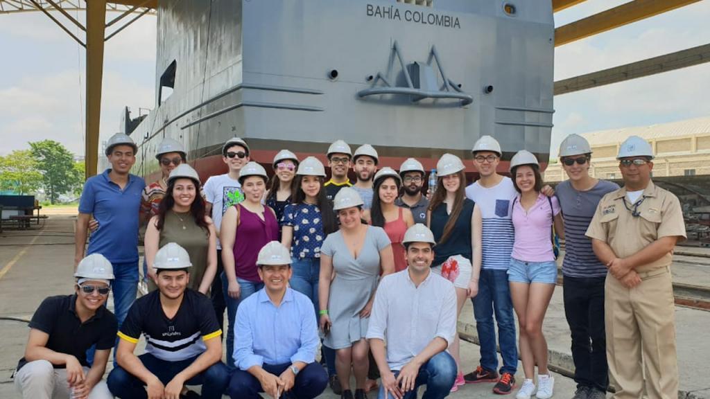Retrato de un grupo de estudiantes con cascos de ingeniería acompañados por integrante de la Armada Nacional