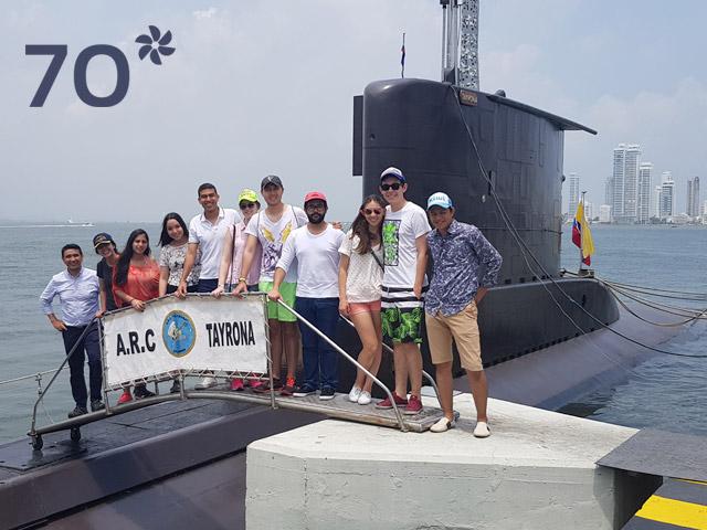 Retrato de jóvenes que posan sobre un submarino.