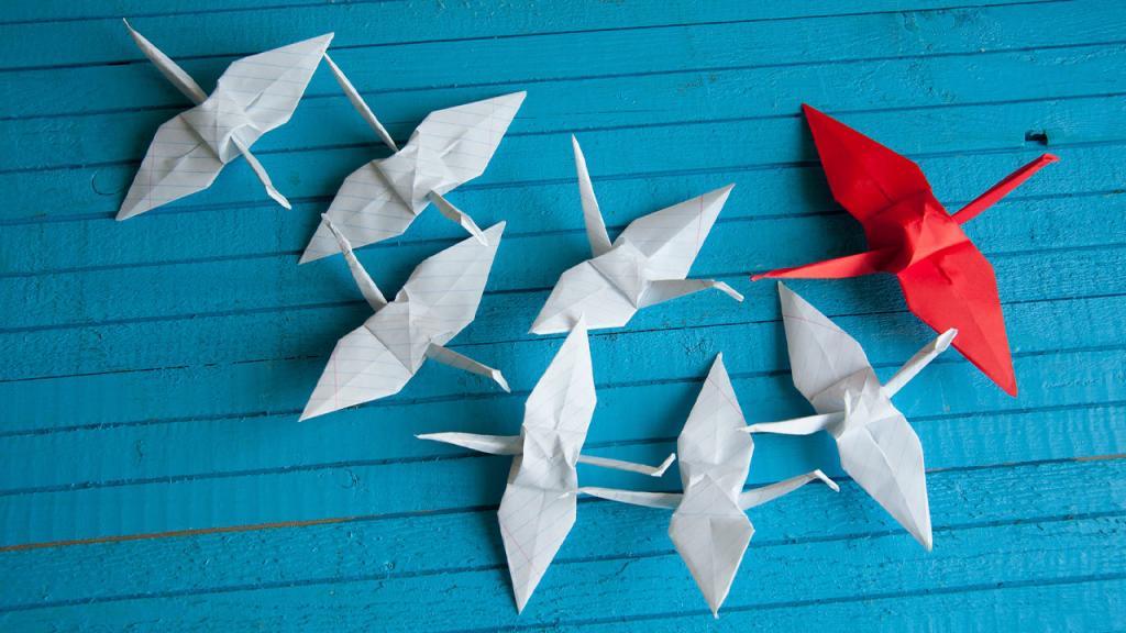 Pájaros de origami sobre una superficie azul.