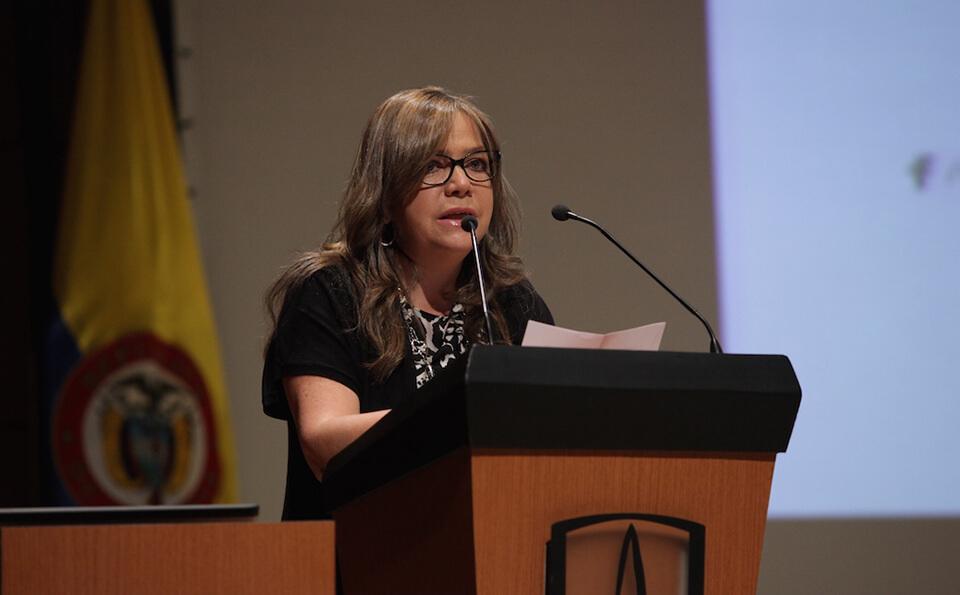 una mujer de saco negro con gafas da un discurso