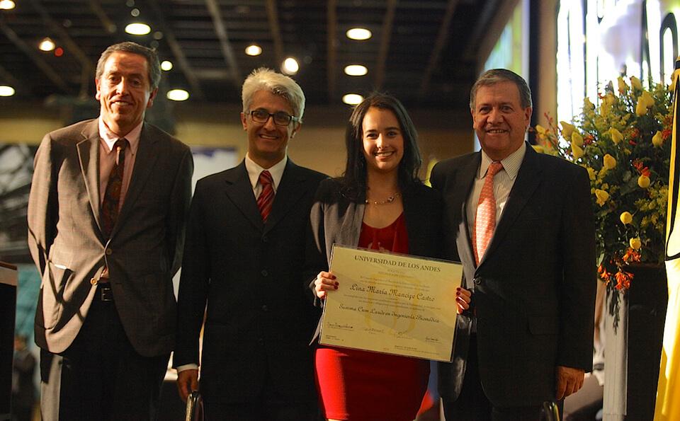 una joven de vestido rojo con chaqueta negra muestra su diploma de grado acompañada de tres hombres