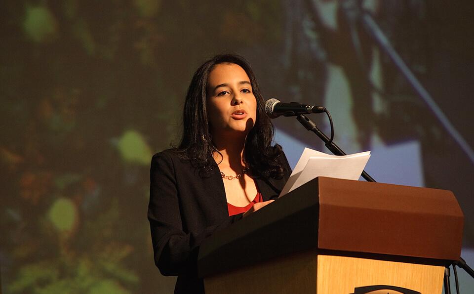 una joven de vestido rojo con chaqueta habla frente a un atril dando un discurso