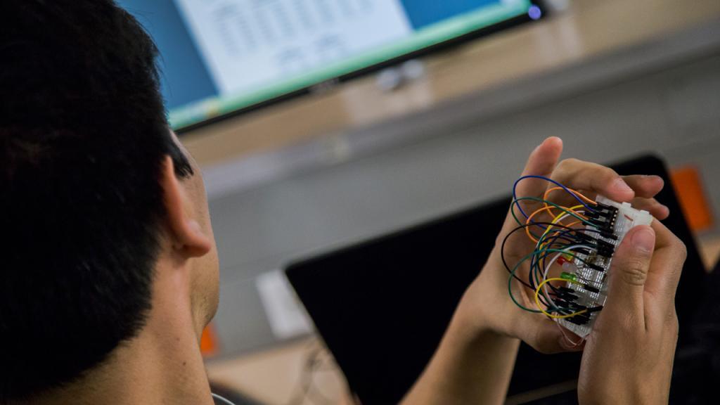 Estudiante sostiene un circuito en la mano