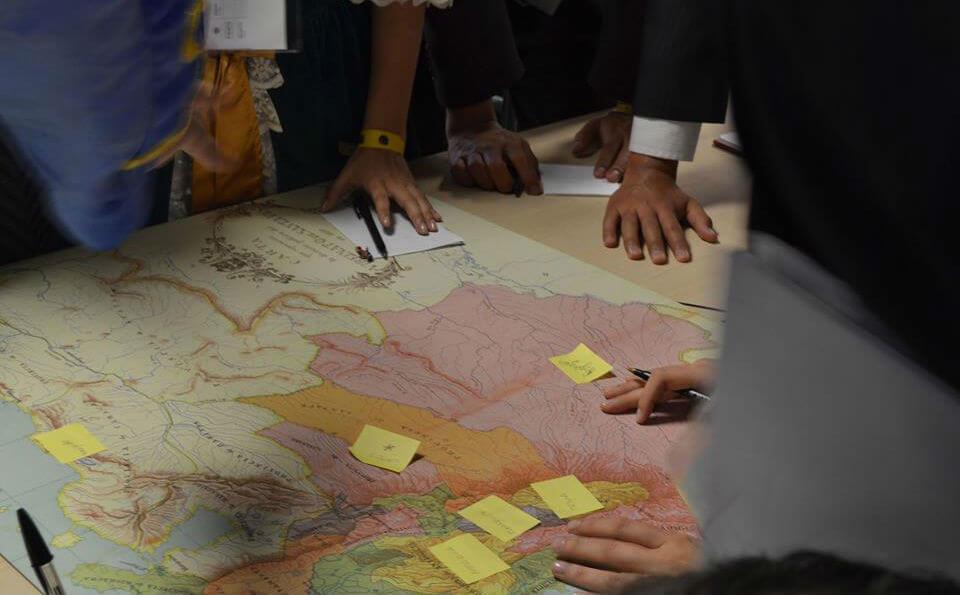 mapamundi sobre una mesa, hay manos sobre el mapa pegando notas amarillas