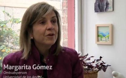 mujer mayor vestida de saco violeta en una oficina