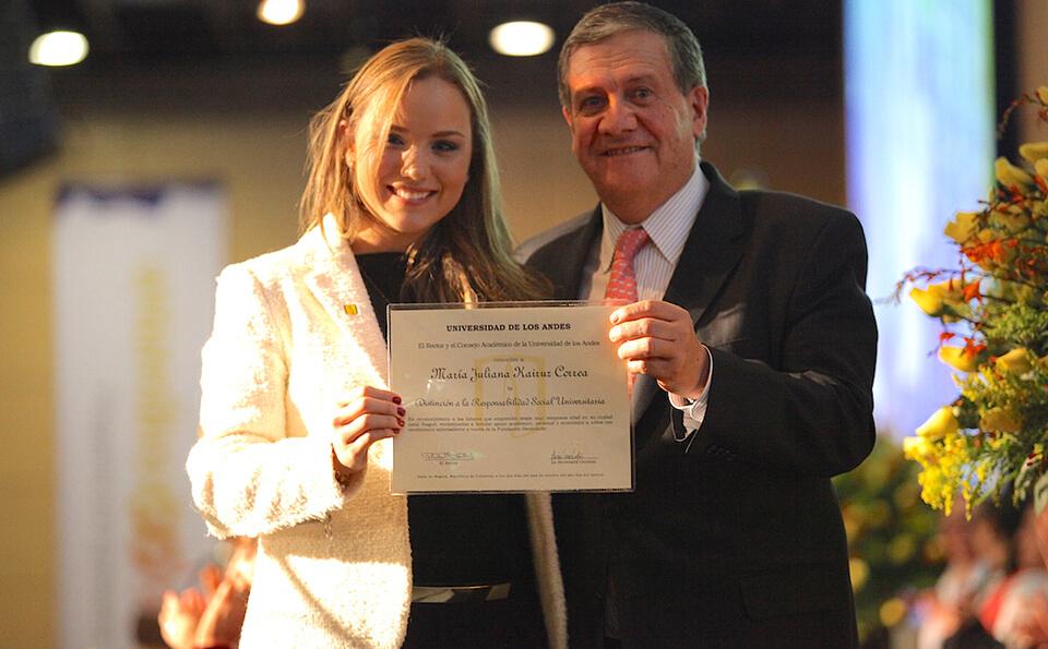 una joven rubia con chaqueta blanca exhibe diploma junto a un hombre mayor de traje