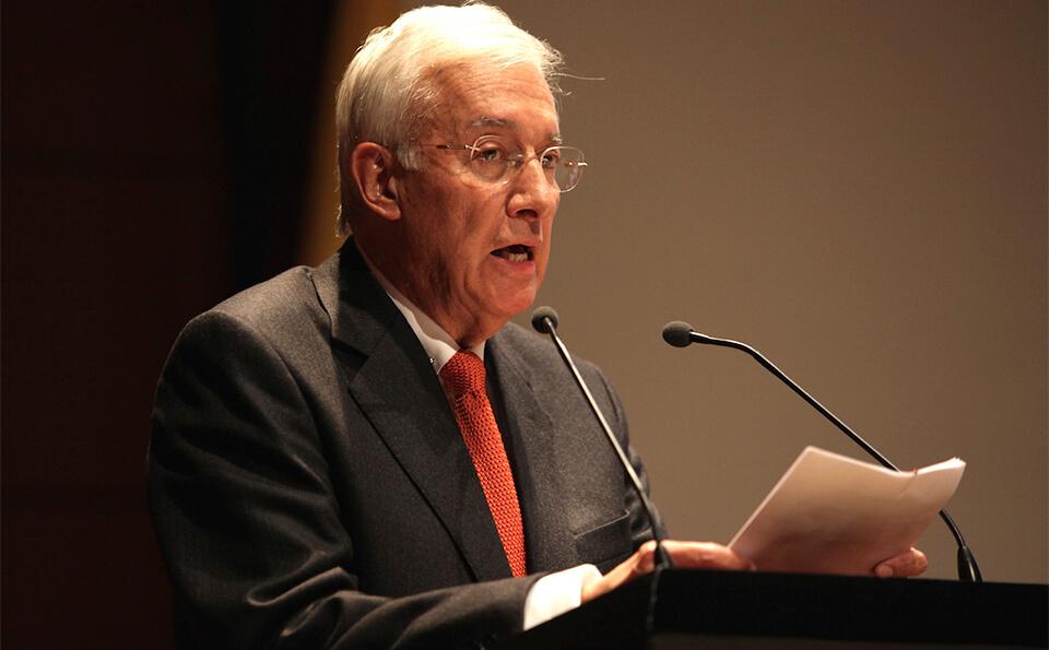 un hombre canoso mayor habla frente a un micrófono en un auditorio